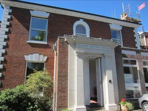 Red brick classical villa with a simple doorway surrounded by stone pillars reading Quaker Meeting House.