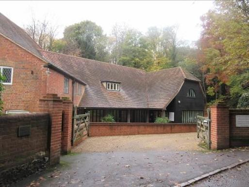 Brick dwelling with long sweeping roof and gated driveway to front.