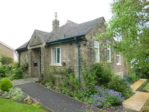 Attractive compact stone building with well-tended garden and stone walls.