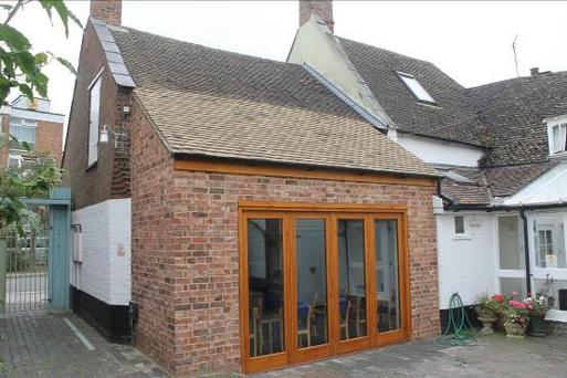 White cottage with modern brick extension containing long windows for the meeting room