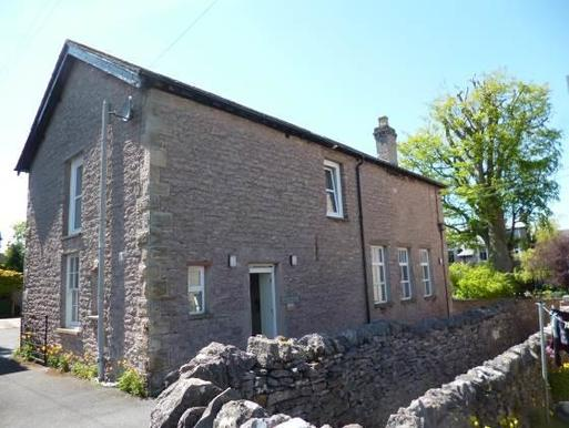 Former stable building is surrounded by stone boundary wall and garden grounds.