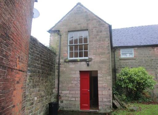 Small stone building with single large window and red front doors.