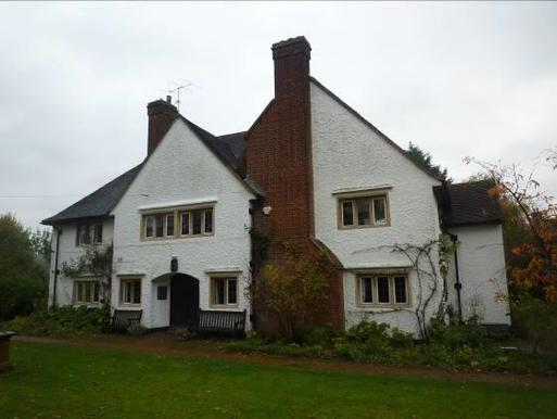 Grand white painted house with large chimney stack and multiple double-span windows, within large gardens.