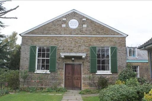 Well-presented meeting house with green shutters and attached burial area.