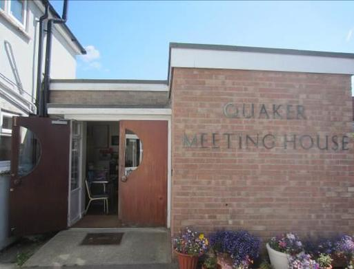 Small brick building with 'Quaker Meeting House' lettering, flowering plants in large pots sit alongside the entrance doors.