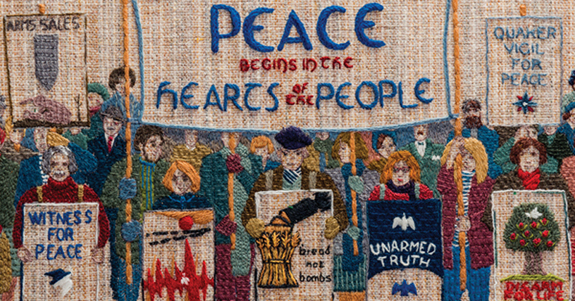 colourful panel of tapestry says Peace begins in the hearts of the people includes dozen figures with placards