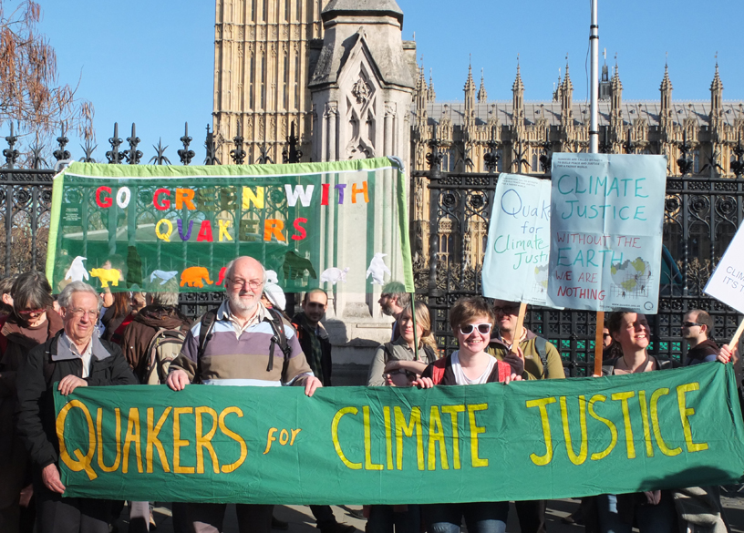 Quakers outside parliament holding green banner, says Quakers for climate justice