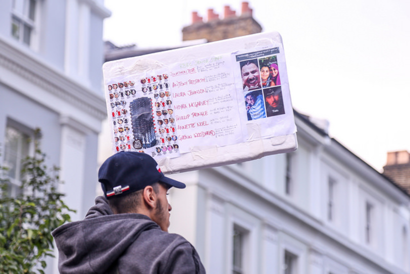 A man holds up the names of those who died in the Grenfell Tower fire. Image: Wasi Daniju/Flickr