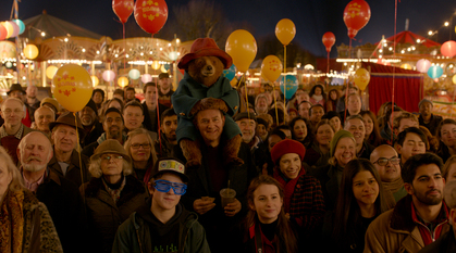 A bear in clothes sits on middle-aged man's shoulders in a crowd of people with balloons, all looking at something.