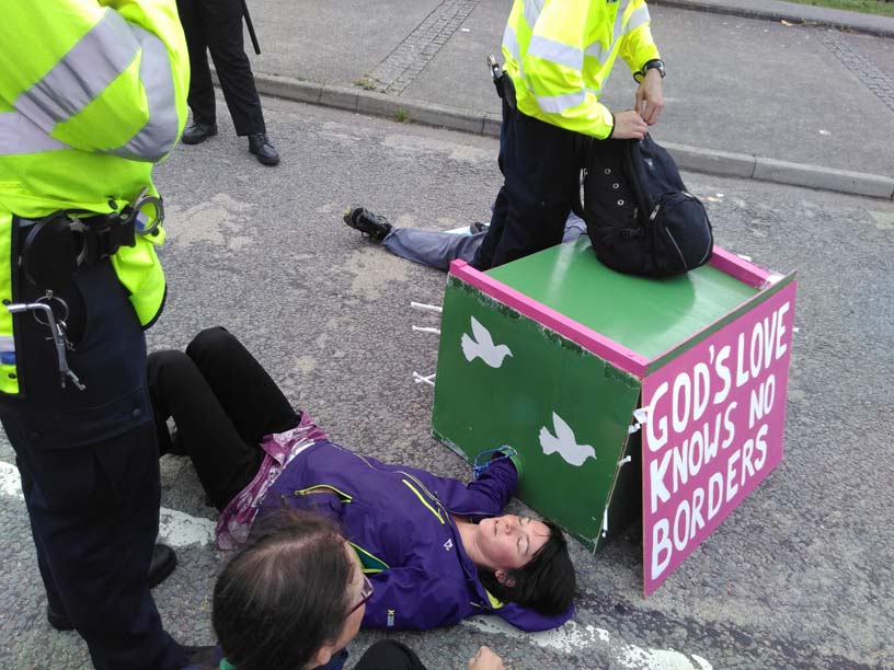 woman lies on ground surrounded by police