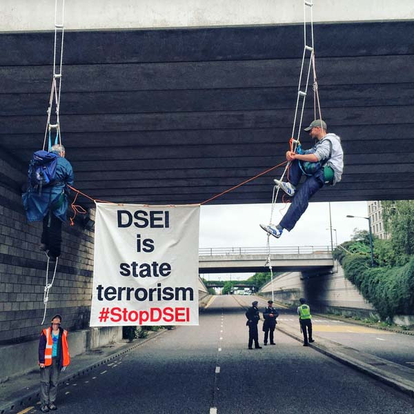 two men abseiling from bridge holding banner says DSEI is state terrorism  #StopDSEI