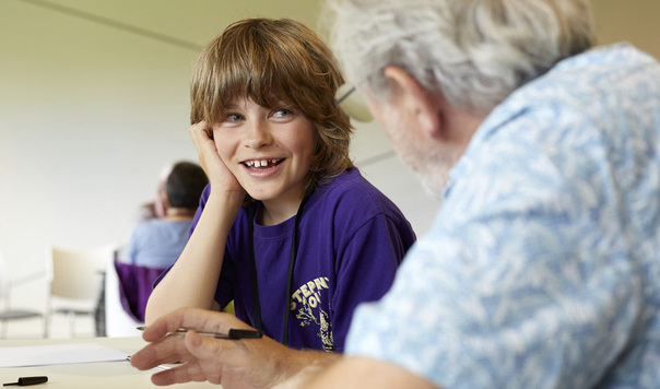 Child smiling and listening to an older person