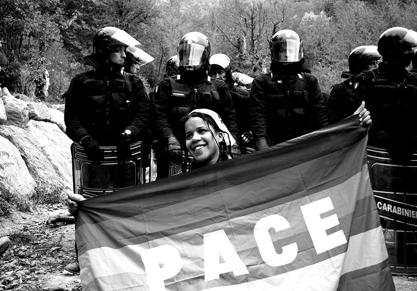 Woman with peace flag in front of police
