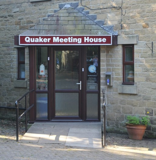 Grey stone building entrance with 'Quaker Meeting House' written above it.
