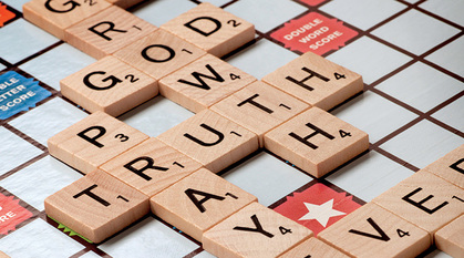 A scrabble board with the words God, growth, truth, prayer, believer spelt out.