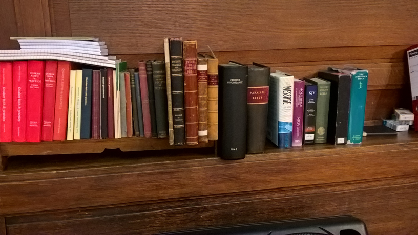 the red book alongside bibles on shelf