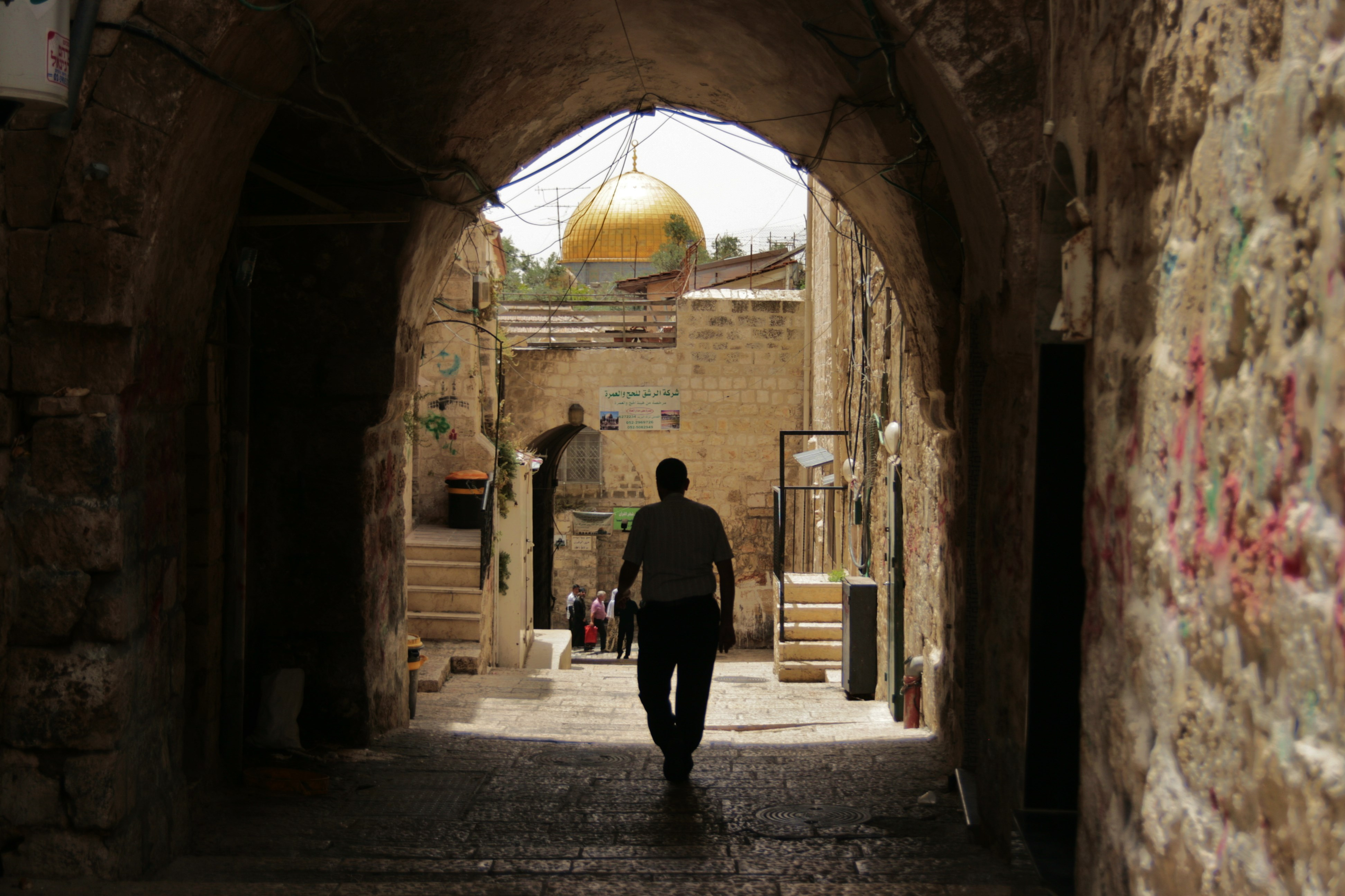 A person in shadow walking through into the light with the golden dome of a mosque shining in the sunlight