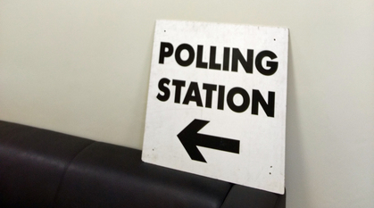 A polling stations sign propped up on the pack of a chair