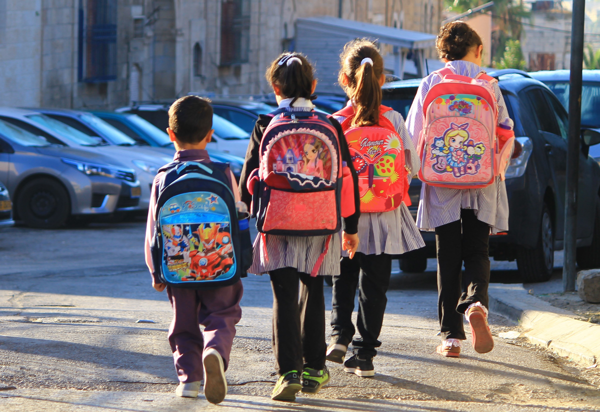 Four children wearing school uniform and carrying backpacks walking to school
