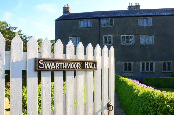 Gate with a sign saying 'Swarthmoor Hall' on it. Gate leads to a large old house.