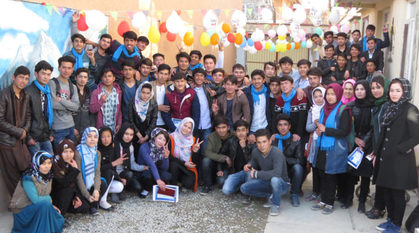 A group of Afghan peace volunteers in a courtyard with balloons. Several are making the peace sign 'v' with their fingers