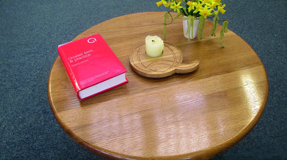 A picture of a wooden table with a handmade 'Q' candle holder, flowers, and Quaker Faith and Practice