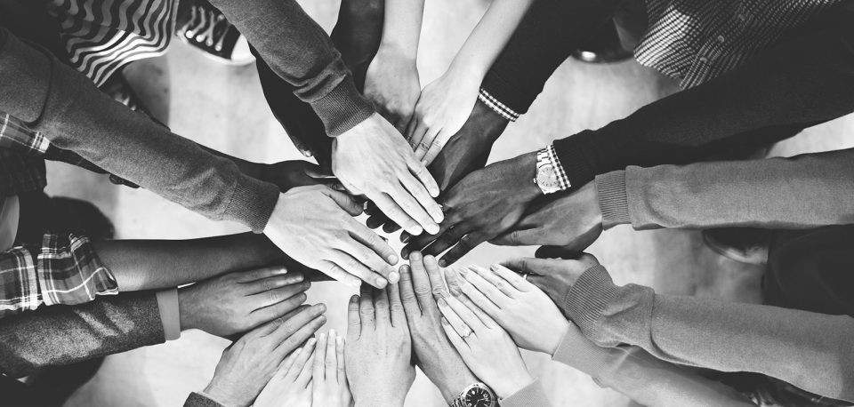 Black and white photo of hands meeting in a circle.