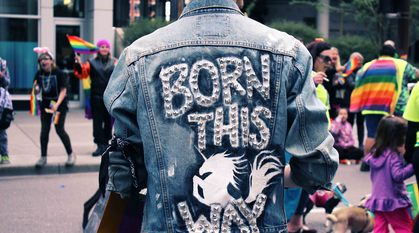 Person wearing a denim jacket with 'born this way' written on the back with a rampant unicorn, standing by the side of family-friendly pride event with lots of rainbow flags around.