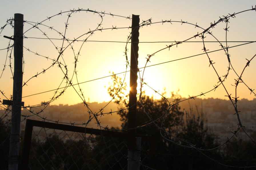 sunset through coils of barbed wire