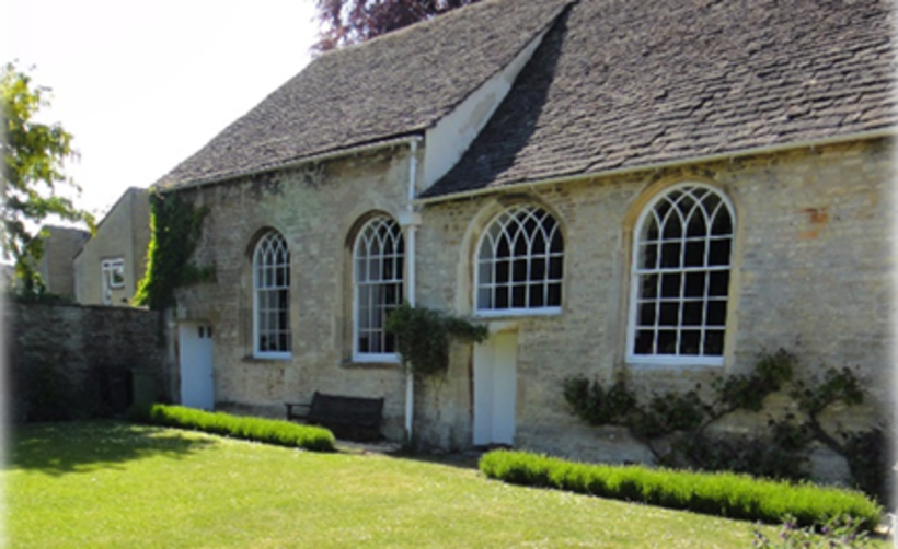 a stone building with large windows photographed from a summer garden.