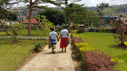 Two women walking down a path holding hands