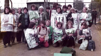 Quaker women outside the fence at RAF Greenham Common wearing and carrying posters and banners about supporting peace and against dropping bombs.