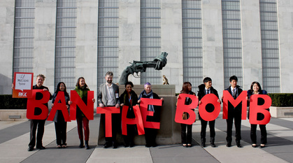 People standing in front of the statue outside the UN of a gun with its barrel tied in a knot, holding up letters spelling out 'ban the bomb'