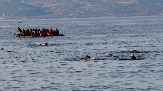 People crowded into a small boat on the sea. Some people swimming around it