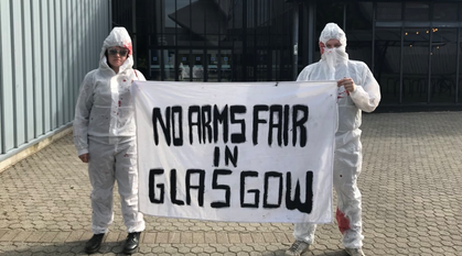 two people in 'blood' spattered hazmat suits holding a banner saying 'no arms fair in Glasgow'