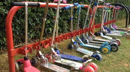a red scooter rack full of children's scooters in lots of different colours