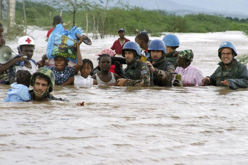 women + children carried across flooded river by blue helmeted UN