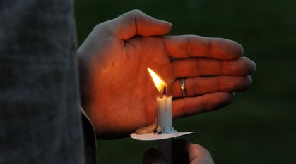 hands holding a lit candle and cupping it from the wind