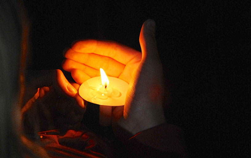 prayerful candle in cupped hands