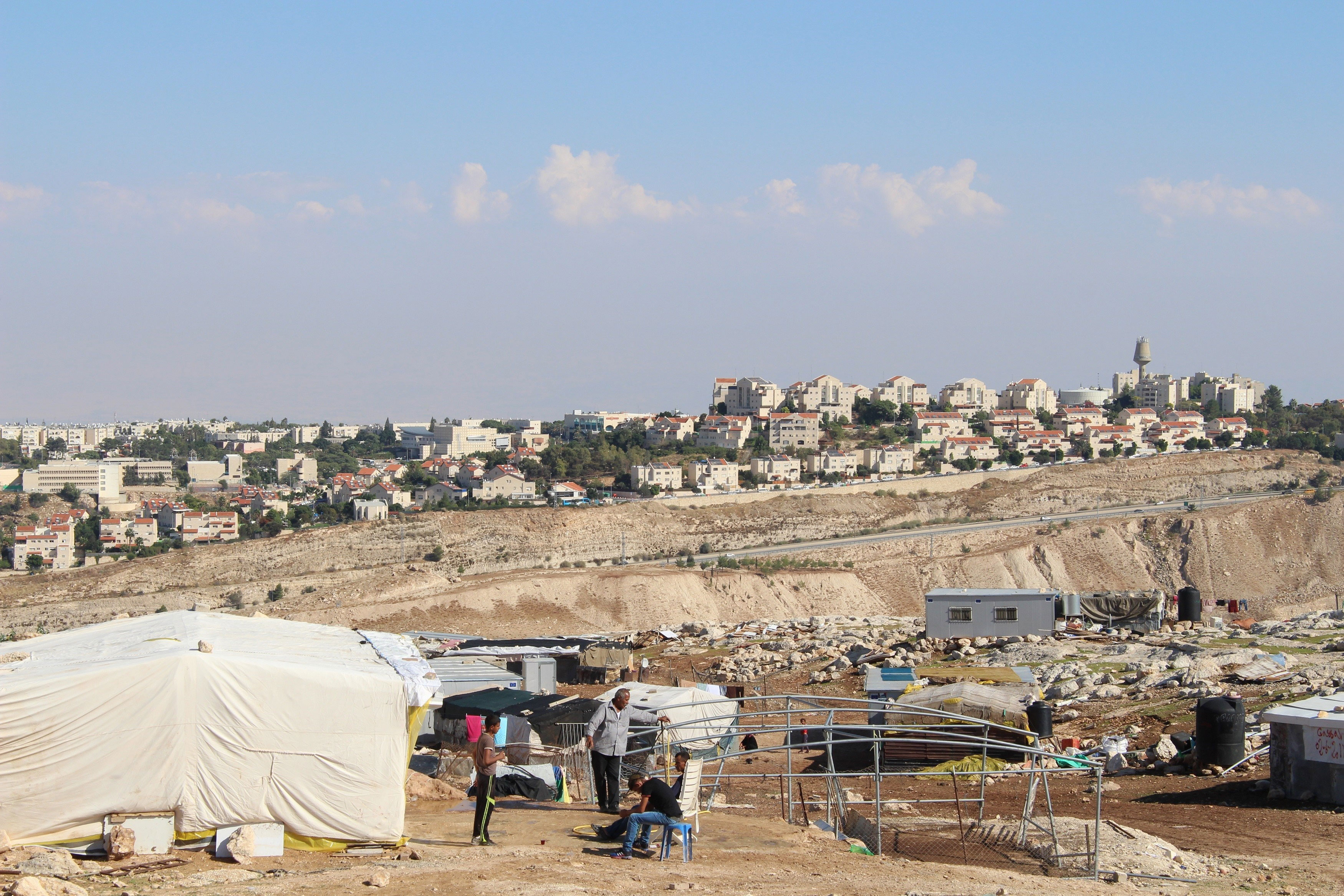 Palestinian tents with settlement behind