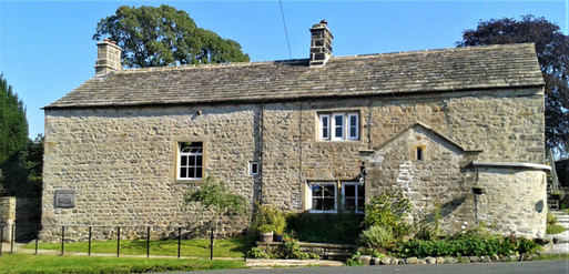 Large stone detached house with four small white-framed windows.