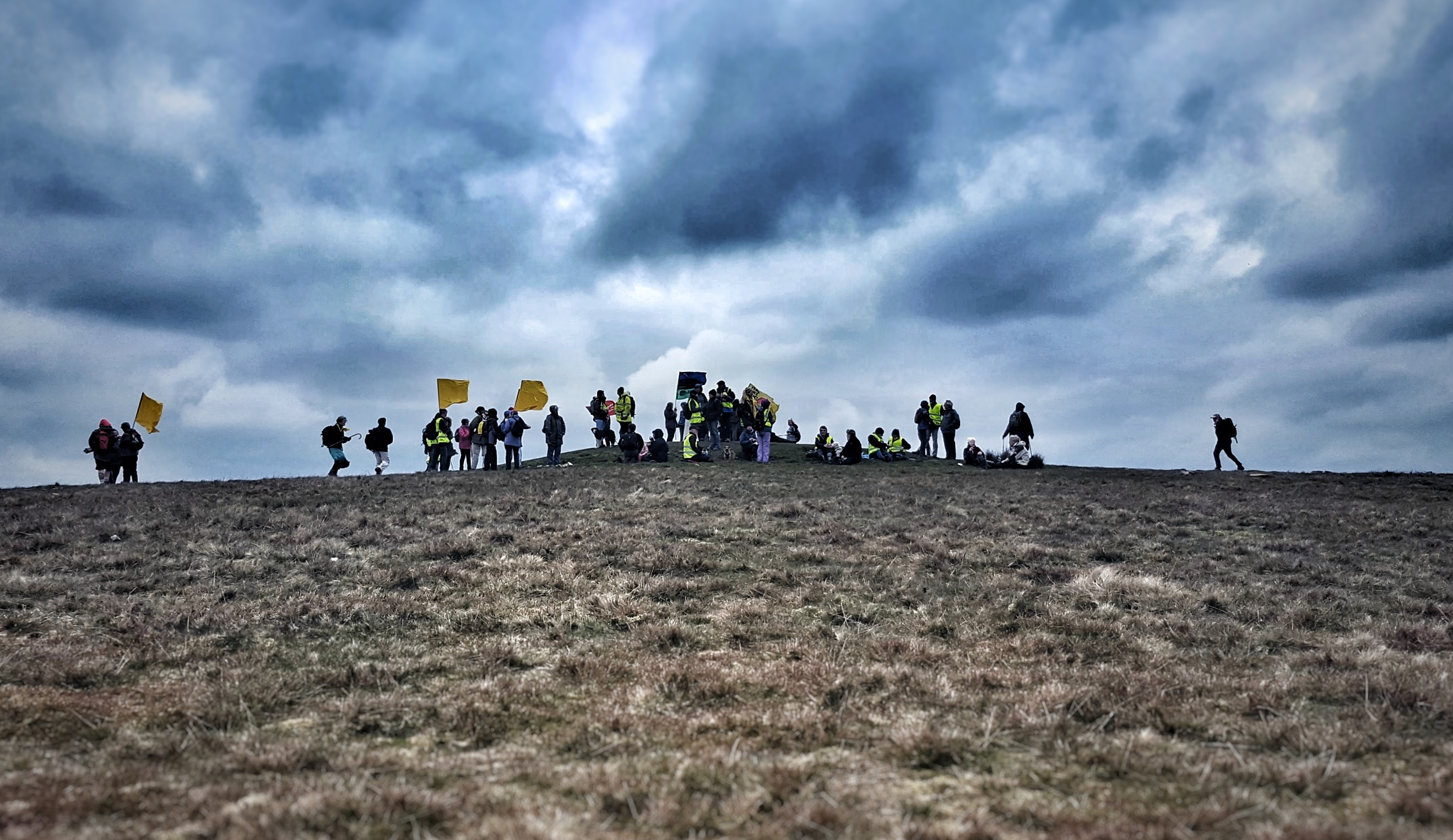 crest of a hill with a dramatic skyline and people gathering at the top