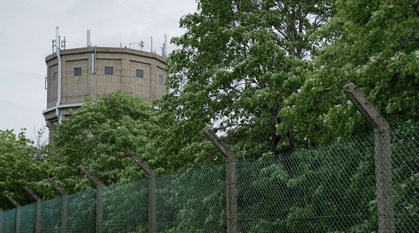 a chain link fence in front of some leafy trees. A watchtower looms in the background.