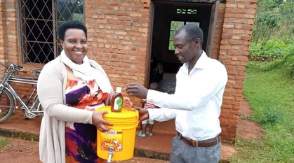a woman holds a bucket with a tap at the bottom and a bottle of dettol sit on top of the sealed bucket. A man is washing his hands.