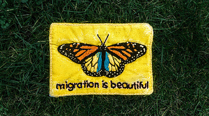 Homemade embroidered butterfly on a bright yellow background with words 'migration is beautiful'