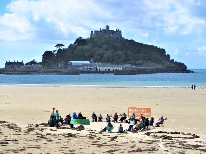 circle of seated Qs on beach near St Michael's Mount